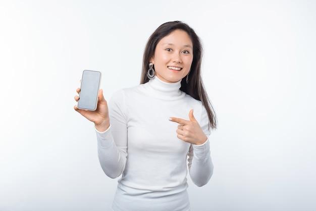 Fotografia młoda szczęśliwa kobieta wskazuje przy smartphone podczas gdy stojący nad białym tłem