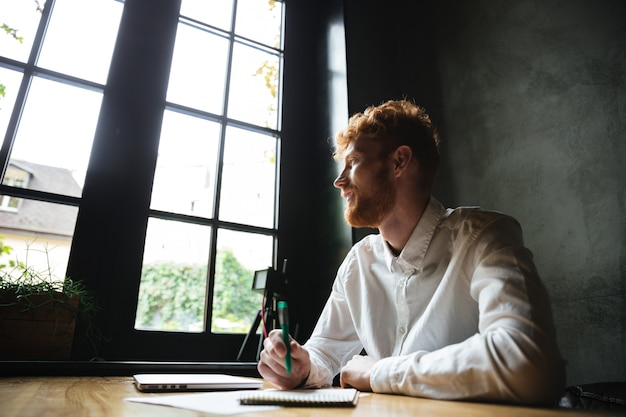 Fotografia młodego uśmiechniętego przystojnego readhead brodaty mężczyzna siedzi na miejscu pracy w domu, patrzejący dużego okno