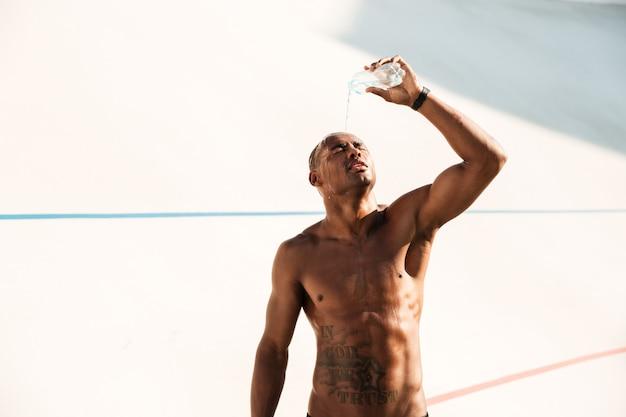Fotografia młody afrykański sporta mężczyzna nalewa out wodę na jego głowie