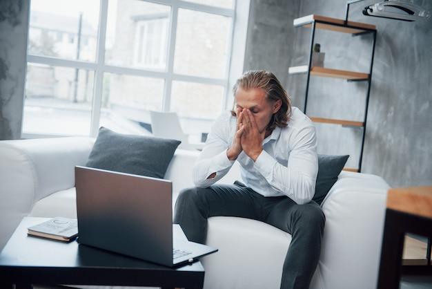 Fotografia młody biznesmena obsiadanie na trenerze i stresujący się out przy pracą