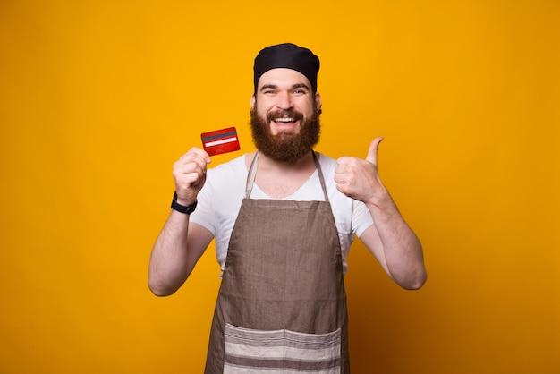 Fotografia młody szczęśliwy szef kuchni pokazuje czerwoną kredytową kartę podczas gdy stojący