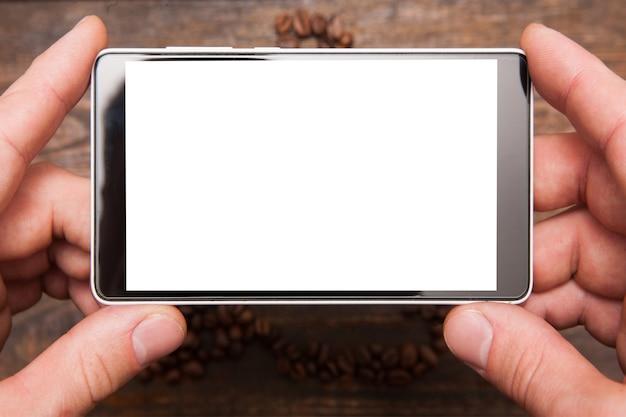 Fotografia mobilna. pusty telefon z ekranem dotykowym w ręce na drewnianym tle. widok z góry biały ekran lcd, zbliżenie.