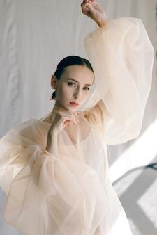 Fotografia modowa młodej zmysłowej damy w latającej sukience piękna dziewczyna pozuje w studio