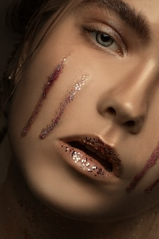 Fotografia mody brunetki piękna młoda dziewczyna ze stylowym makijażem z łezkami brokatu. makijaż, zbliżenie portret w ujęciu, widok kolorów. dodge i burn oraz rozkład częstotliwości.