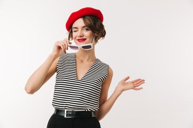 Fotografia mody dama z krótkim ciemnym włosy jest ubranym modnego czerwonego beret i roczników okularów przeciwsłonecznych ono uśmiecha się, odizolowywająca nad bielem