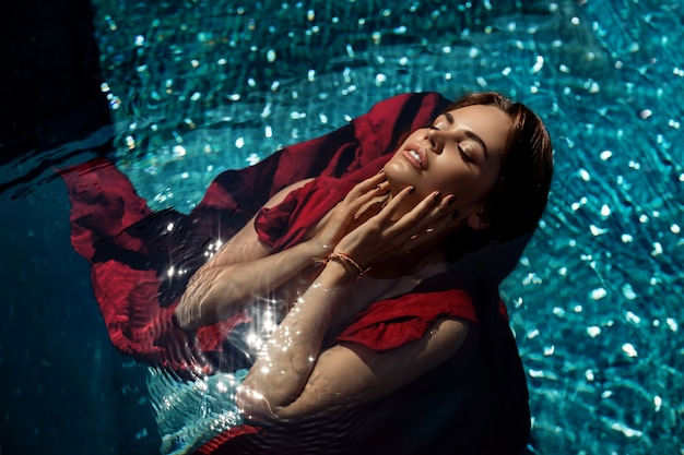 Fotografia mody: dziewczyna z jasnym makijażem w czerwonej sukience leżącej na wodzie basenu.