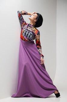 Fotografia mody młodej kobiety w fioletowej sukience