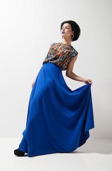 Fotografia mody młodej kobiety w niebieskiej sukience