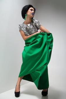 Fotografia mody młodej kobiety w zielonej sukience