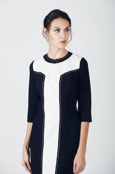 Fotografia mody młodej wspaniałej kobiety w czarnej sukience. dziewczyna