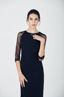 Fotografia mody młodej wspaniałej kobiety w czarnej sukience
