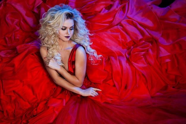 Fotografia mody młodej wspaniałej kobiety w czerwonej sukience. portret studyjny
