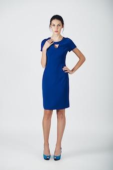 Fotografia mody młodej wspaniałej kobiety w niebieskiej sukience
