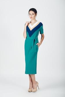 Fotografia mody młodej wspaniałej kobiety w zielonej sukience