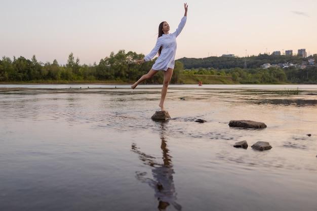 Fotografia mody na zewnątrz pięknej artystycznej damy nad rzeką