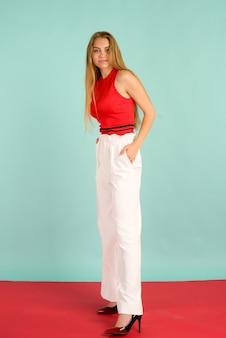 Fotografia mody pięknej eleganckiej młodej kobiety w całkiem czerwony podkoszulek, białe spodnie, wysokie obcasy pozowanie na niebieskim tle.