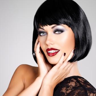 Fotografia mody pięknej kobiety brunetka z zastrzeloną fryzurą. zbliżenie twarzy dziewczyny z czerwonymi ustami i paznokciami