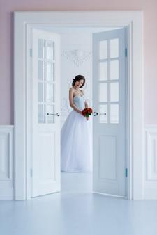 Fotografia mody pięknej panny młodej w jasnym pokoju obok drzwi