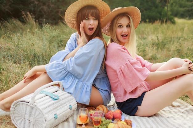 Fotografia mody plenerowej dwóch atrakcyjnych kobiet w słomkowym kapeluszu i letnich ubraniach, które zachwycają piknika.
