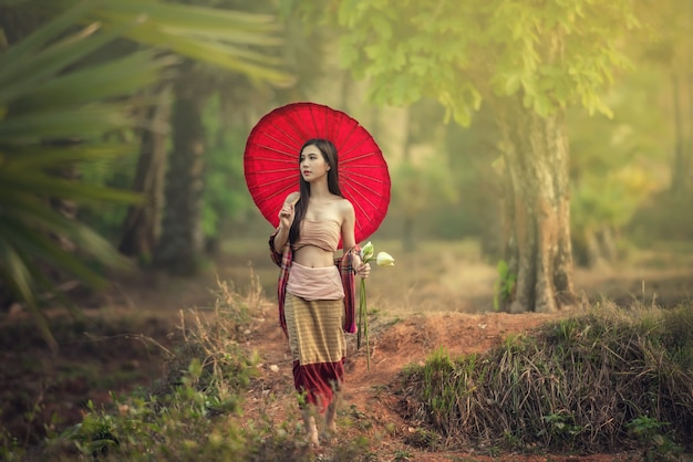 Fotografia mody plenerowej młodej pięknej damy w jesienny krajobraz z suchymi kwiatami.