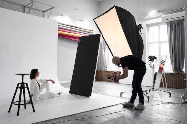 Fotografia mody w studiu fotograficznym. profesjonalny fotograf mężczyzna robi zdjęcia pięknej modelki w aparacie, za kulisami