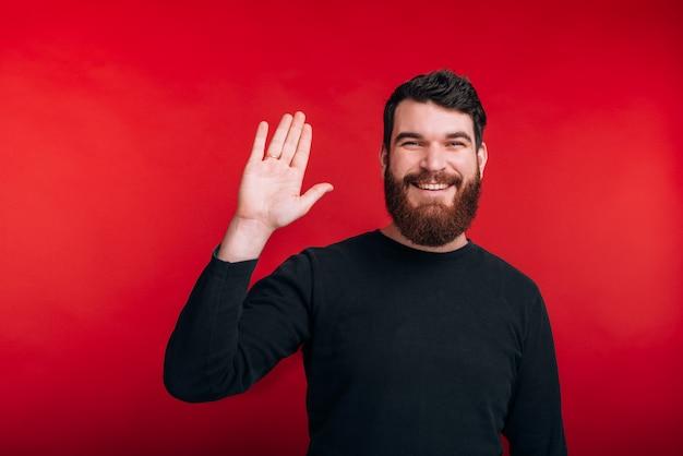 Fotografia Mówi Rozochocony Brodaty Mężczyzna Cześć Podczas Gdy Stojący Nad Czerwieni Przestrzenią Premium Zdjęcia