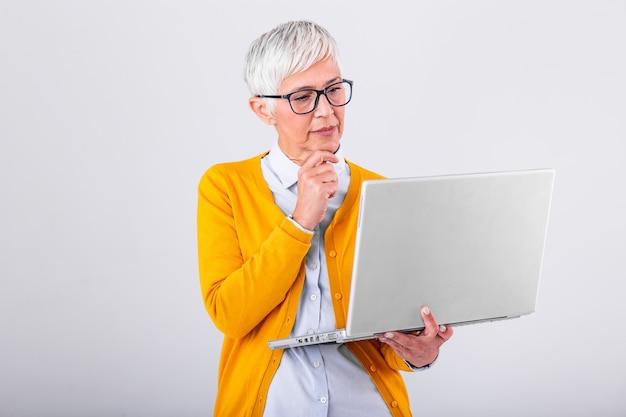 Fotografia myśląca dojrzała biznesowa kobieta odizolowywająca nad szarym tła mienia laptopem. wizerunek zmieszana starsza kobieta używa laptop.