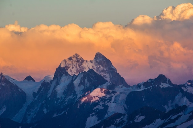 Fotografia piękne góry przy zmierzchem w chmurach