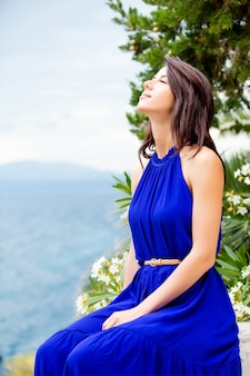 Fotografia piękny młodej kobiety obsiadanie na schodkach zbliża kwitnącego drzewa w grecja