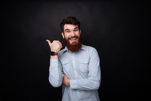 Fotografia pokazuje kciuk up brodaty mężczyzna i ono uśmiecha się przy kamerą nad zmrokiem odizolowywał bcakground