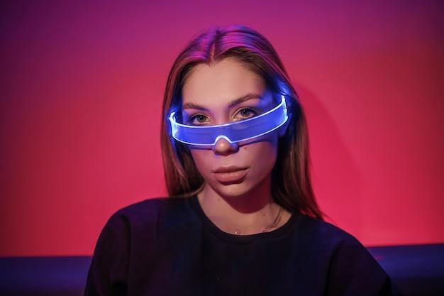 Fotografia portretowa nocna w stylu cyberpunk, kobieta w okularach, android-robot-cyborg kobieta, w futurystycznym cyberpunkowym stroju modowym