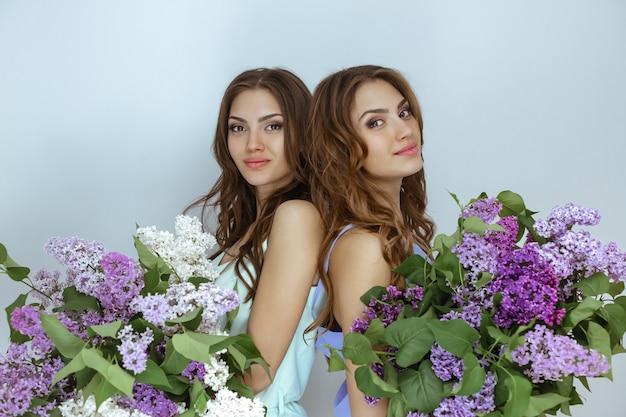 Fotografia portretowa studyjnej mody dwóch bliźniaczek z bukietem wiosennych kwiatów