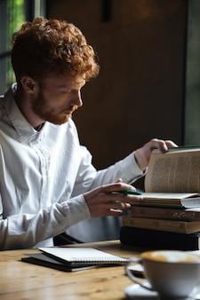 Fotografia poważnej rudzielec brodaty uczeń, przygotowywa do egzaminu w kawiarni