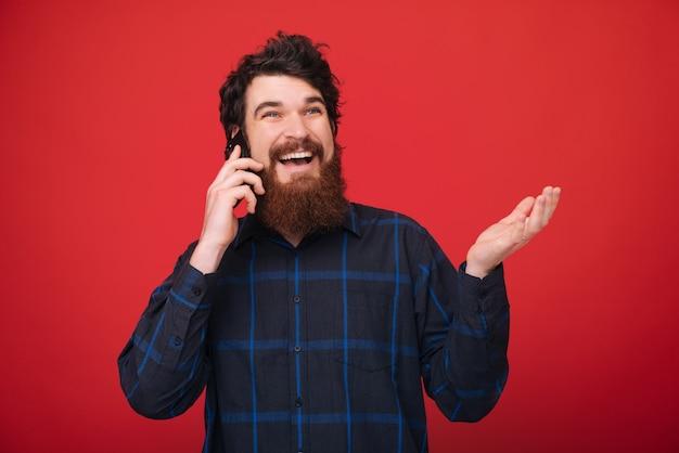 Fotografia przystojny facet opowiada na telefonie nad czerwieni ścianą z brodą