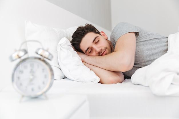 Fotografia przystojny mężczyzna ma ścierń i jest ubranym przypadkowych ubrania, śpi w domu w łóżku z zegarem na nocnym stoliku
