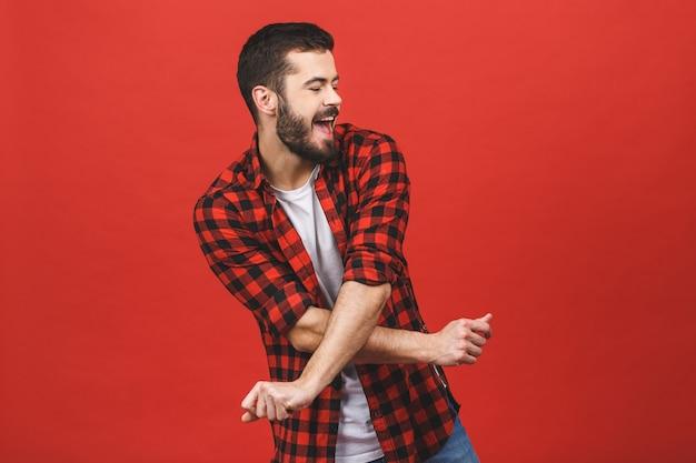 Fotografia przystojny młodego człowieka taniec odizolowywający nad czerwieni ścianą.