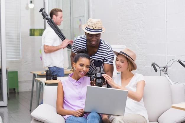 Fotografia redaktorzy używa laptop podczas gdy patrzejący kamerę w studiu