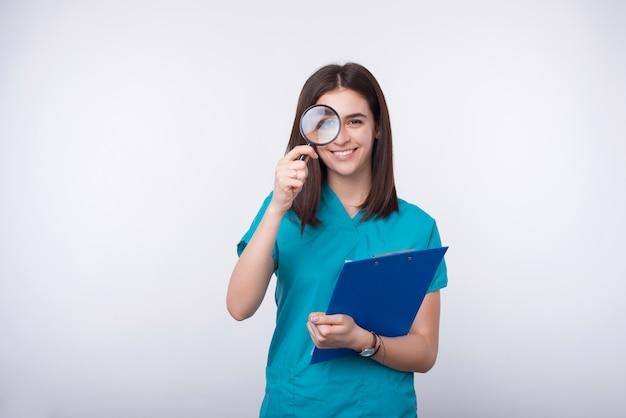Fotografia rozochocona młoda kobieta patrzeje przez powiększać - szkło i trzyma papierową deskę na biel przestrzeni.