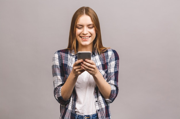 Fotografia rozochocona śliczna piękna młoda kobieta gawędzi telefonem komórkowym odizolowywającym nad szarości ściany ścianą.