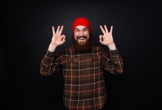 Fotografia rozochocony mężczyzna z brodą i czerwień kapeluszem robi ok podpisuje odosobnioną zmrok ścianę