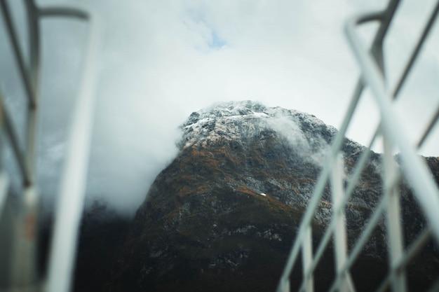 Fotografia selektywna ostrości wysokich gór skalistych pokrytych śniegiem i mgłą