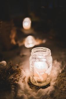 Fotografia selektywnej ostrości zapalonych świec w słoiku mason