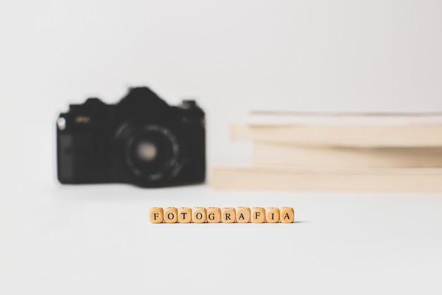 Fotografia słowo drewnianymi literami z książkami i aparatem fotograficznym na białym tle