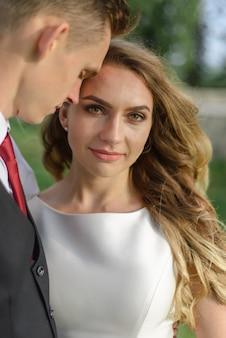 Fotografia ślubna. mężczyzna pochylił głowę do swojej kobiety. panna młoda i pan młody