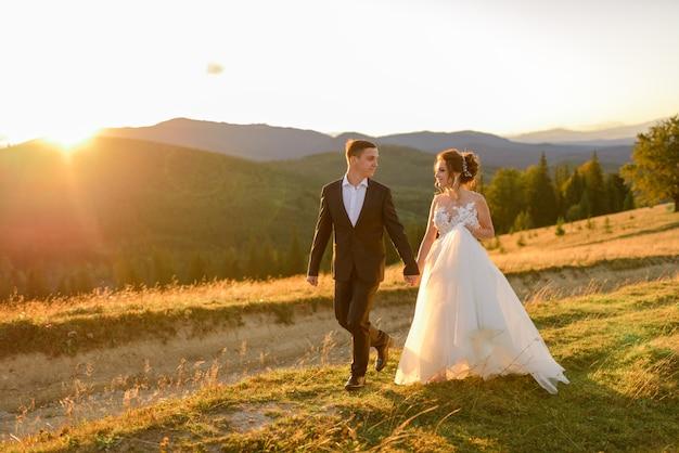 Fotografia ślubna w górach. panna młoda i pan młody trzymają rękę i chodzą o zachodzie słońca.