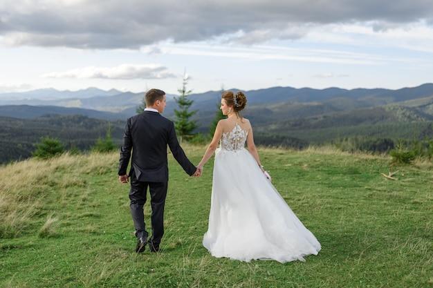Fotografia ślubna w górach. panna młoda i pan młody trzymają rękę. mężczyzna prowadzi kobietę.