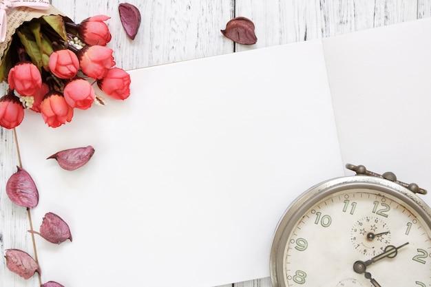 Fotografia stock mieszkanie kłaść rocznika biel malującego drewna stołu purpurowych kwiatów płatków rocznika budzika czerwieni róża