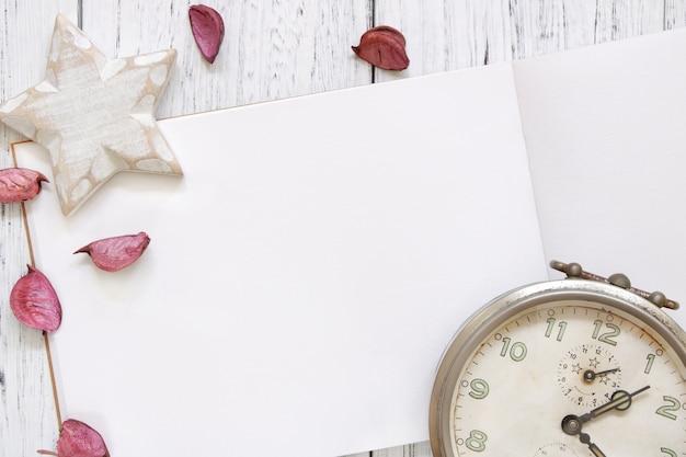 Fotografia stock mieszkanie kłaść rocznika biel malującego drewna stołu purpurowych kwiatów płatków rocznika budzika gwiazdy rzemiosło