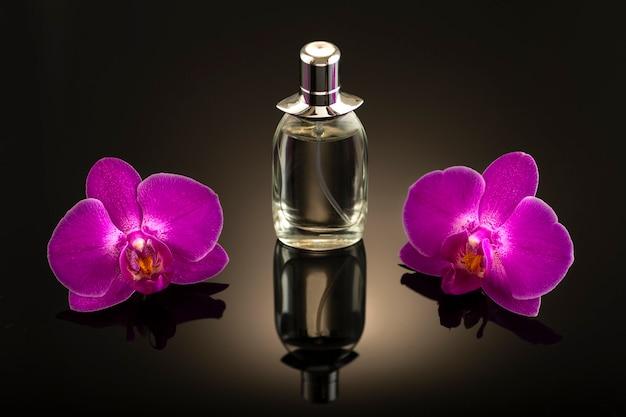 Fotografia studyjna, butelka perfum z dwoma różowymi kwiatami orchidei na ciemnej powierzchni bez tytułu