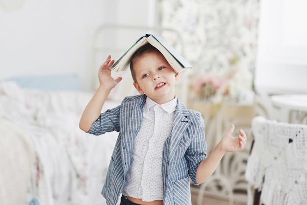 Fotografia sumienny uczeń z książką na głowie robi pracie domowej. uczeń ma dość odrabiania lekcji